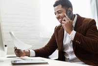 African American businessman talking on cell phone in office