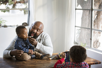 Father feeding baby son at table