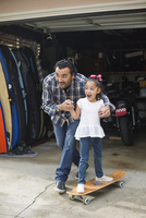 Hispanic father teaching daughter to ride skateboard