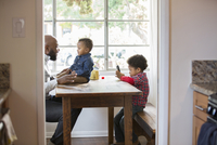 Father and children sitting at table