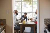 Fathers and children sitting at table