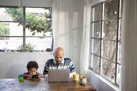 Mixed race father and son using technology at table