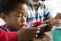 Mixed race boy using cell phone at table