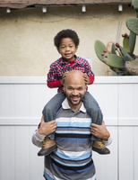 Mixed race father carrying son on shoulders