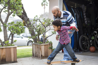 Mixed race father teaching son to ride skateboard outdoors