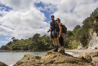 Caucasian couple hiking on remote beach