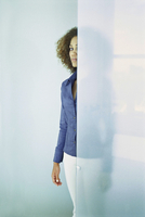 Black businesswoman standing behind glass wall