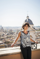 Caucasian woman standing on urban rooftop, Rome, Roma, Italy