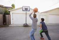 Caucasian brothers playing basketball near garage