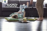 Caucasian couple using digital tablets on floor 11018070152| 写真素材・ストックフォト・画像・イラスト素材|アマナイメージズ
