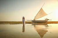 Pacific Islander woman admiring boat on beach