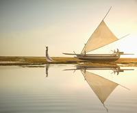 Pacific Islander woman standing near boat on beach