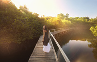 Pacific Islander woman walking on wooden dock at river