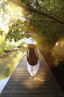 Pacific Islander woman on wooden dock at river