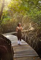 Pacific Islander woman photographing on walkway in jungle 11018070325| 写真素材・ストックフォト・画像・イラスト素材|アマナイメージズ