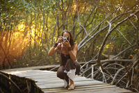 Pacific Islander woman photographing on walkway in jungle 11018070326| 写真素材・ストックフォト・画像・イラスト素材|アマナイメージズ