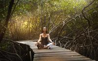 Pacific Islander woman meditating on walkway in jungle 11018070329| 写真素材・ストックフォト・画像・イラスト素材|アマナイメージズ
