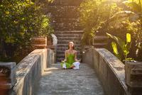 Pacific Islander woman meditating on walkway in jungle 11018070352| 写真素材・ストックフォト・画像・イラスト素材|アマナイメージズ