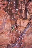 Mixed race teenage girl rock climbing on cliff