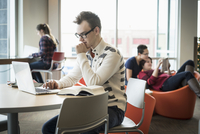 Teenage boy using laptop in library