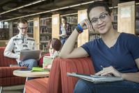 Teenage girl studying in library 11018070593| 写真素材・ストックフォト・画像・イラスト素材|アマナイメージズ
