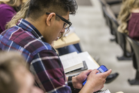 Hispanic college student using cell phone in classroom