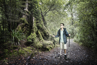 Mixed race boy hiking in forest
