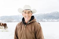 Caucasian farmer smiling in snowy field 11018070817| 写真素材・ストックフォト・画像・イラスト素材|アマナイメージズ