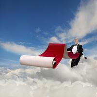 Caucasian waiter rolling out red carpet in sky 11018070884| 写真素材・ストックフォト・画像・イラスト素材|アマナイメージズ