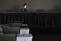 Businesswoman using cell phone in convention room