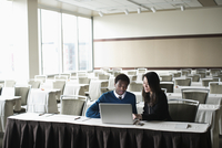 Business people using laptop in convention room