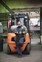 Worker using cell phone near forklift in factory