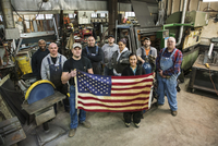 High angle view of workers holding American flag in factory