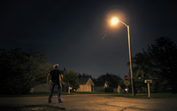 Caucasian man looking up at street light in suburb at night
