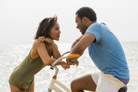 Couple talking on beach with bicycle