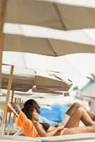 Couple laying on deck chairs on beach
