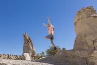 Caucasian girl jumping off rock formation 11018071201| 写真素材・ストックフォト・画像・イラスト素材|アマナイメージズ