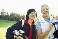 Women carrying golf clubs on golf course