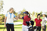 Women high-fiving on golf course