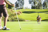 Women planning putt on green at golf course