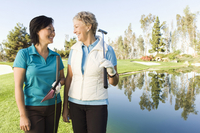 Women laughing on golf course near water hazard