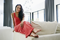 Chinese woman smiling on sofa