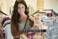 Caucasian mother and baby daughter shopping in clothing store 11018071402| 写真素材・ストックフォト・画像・イラスト素材|アマナイメージズ