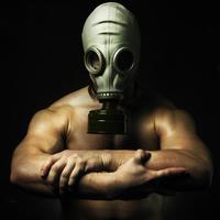 Nude Caucasian man wearing gas mask