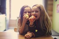 Caucasian girls eating healthy snack 11018071487| 写真素材・ストックフォト・画像・イラスト素材|アマナイメージズ
