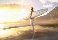Android carrying surfboard on beach