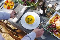Caucasian man setting platter of soup on outdoor table 11018071524| 写真素材・ストックフォト・画像・イラスト素材|アマナイメージズ