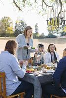 Friends eating at outdoor table 11018071526| 写真素材・ストックフォト・画像・イラスト素材|アマナイメージズ