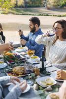 Friends eating at outdoor table 11018071528| 写真素材・ストックフォト・画像・イラスト素材|アマナイメージズ