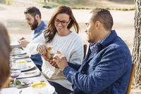 Couple breaking bread at outdoor table 11018071532| 写真素材・ストックフォト・画像・イラスト素材|アマナイメージズ